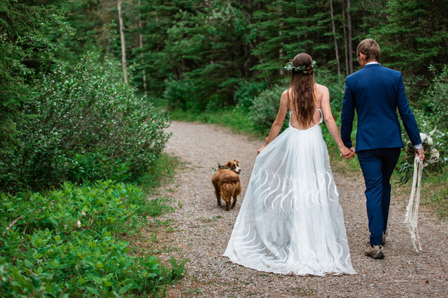 Bride and groom waking down a path with their dog.