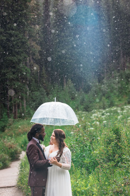Bride and groom standing under a clear umbrella and it is raining.