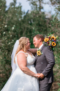 Bride and groom embracing and smiling.