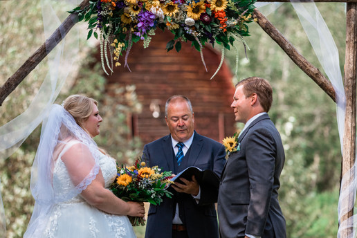 Bride and groom are having their ceremony under an archway.