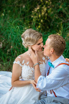 bride and groom embracing, the groom is holding the brides face with one hand.
