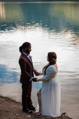 Couple holding hands looking at one another with the water right beside them.