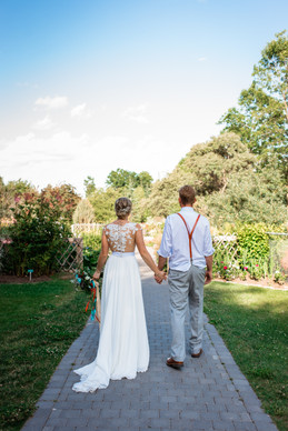 bride and groom walking down a path hand in hand.
