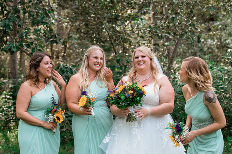 Bride standing with her bridesmaids, all the girls are laughing.
