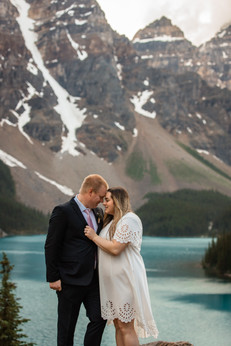 Bride and groom at moraine lake at sunrise, snuggled in close with the valley of 10 peeks in the background.