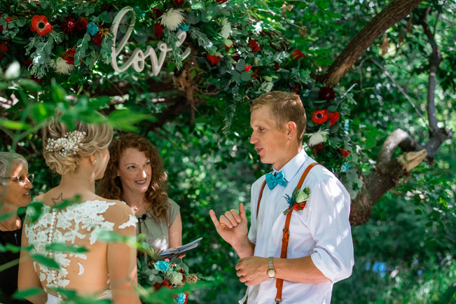 groom signing his vows to his bride under a beautiful tree.