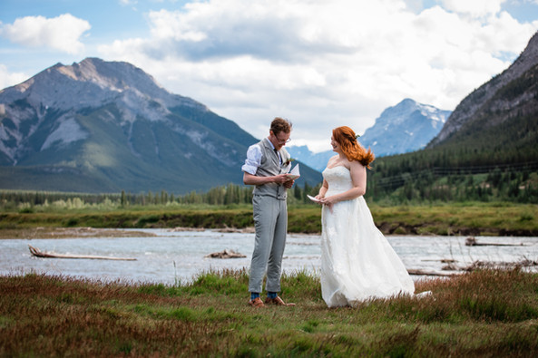 Bride and groom exchanging vows in a valley in Kananaskis Country with the beautiful rocky mountains in behind.