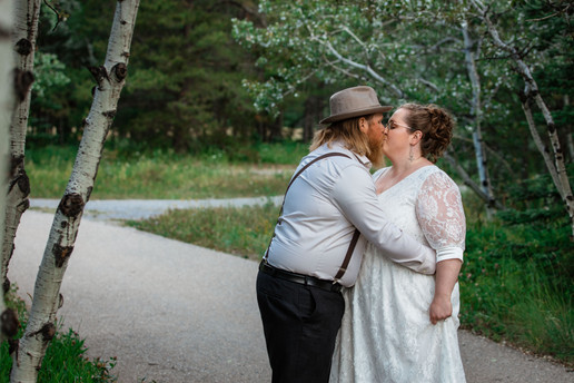 Bride and groom kissing on a pathway. Groom is hugging the bride.