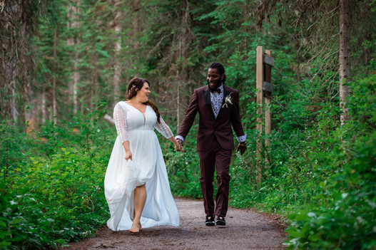 Bride and groom walking together hand in hand on a pathway through bush and trees.