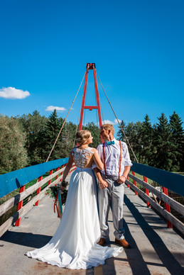 bride and groom walking across a bridge that has blue and orange accent colours the same and their colours. and