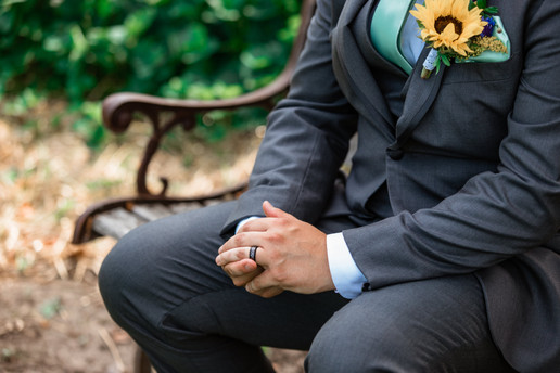 Groom sitting on a metal and wood bench touching his wedding ring.