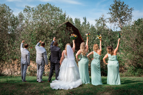 Wedding party holding up hands and bouquets.