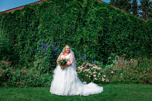 Bride standing in the garden with flowers and greenery all behind her. Brides train in laid out on the grass behind her.
