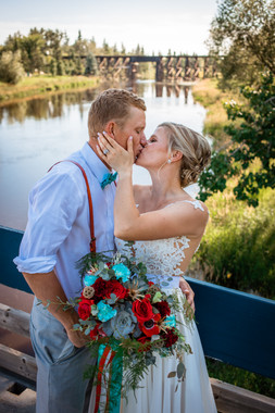 bride and groom kissing while standing on a suspension bridge.