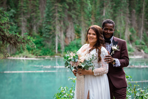 Bride posing in front of the groom and his hand is on her shoulder, Emerald Lake is behind them surrounded by trees.