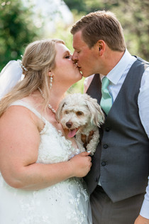 Bride and groom kissing while holding their dog between them.