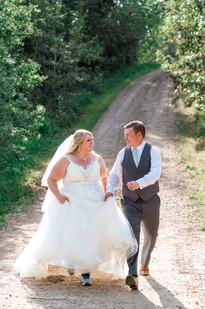 Bride and groom walking down a path holding hands, laughing.