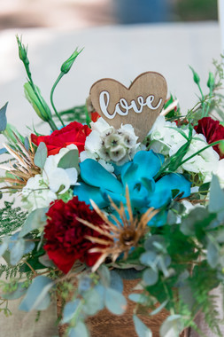 box of with flowers with vibrant colours of blue, white and red with a little wooden love sign.
