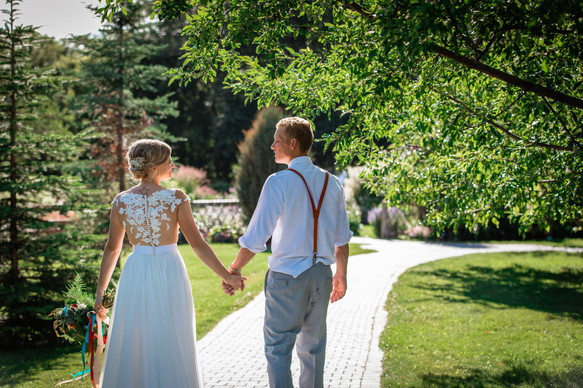 bride and groom walking down a path hand in hand looking at one another.