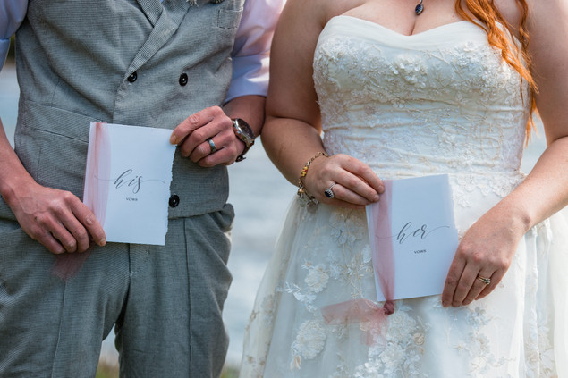 Bride and groom showing their vow booklets.