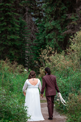 Bride and groom walking on a path into the trees at Emerald Lake.