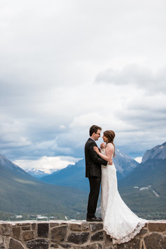Bride and groom dancing with a stunning background of clouds and mountains