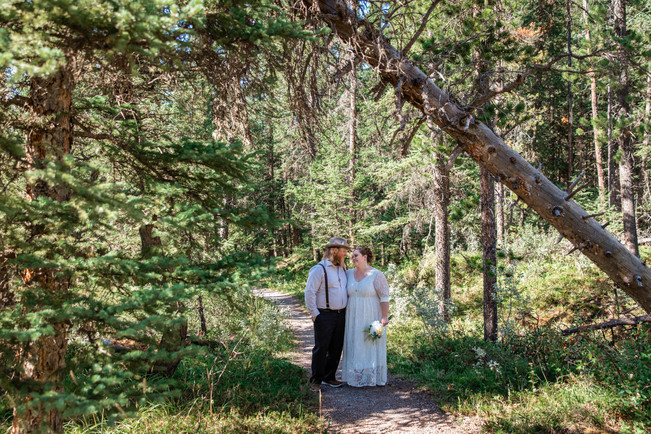 Bride and groom standing on a pathway in the trees.