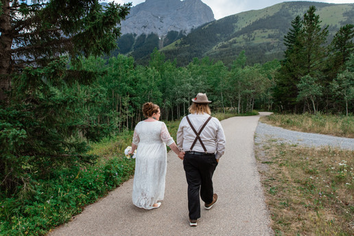Bride and groom walking hand in hand on a path lined with trees.