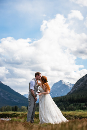 Bride and groom kissing after saying their vows in front of the water with the mountains in the background.