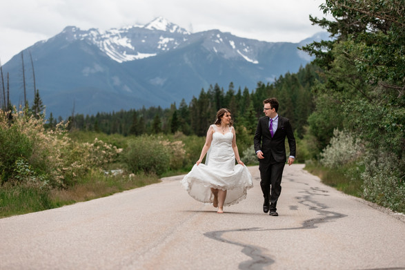Bride and groom walking down a street in Banff National Park, the bride is barefoot