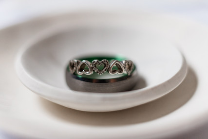 Bridal ring sitting on top of the grooms ring in a little dish up close showing details of the ring which is little hearts and diamonds in the hearts.