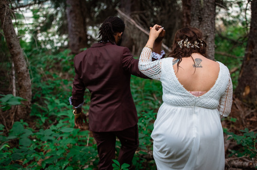 Groom leading his bride by the hand through the tall bush and she is holding up her dress.