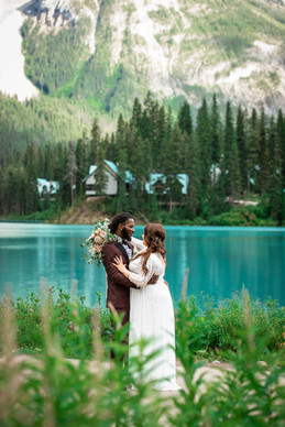 Bride and groom holding one another standing in front of Emerald Lake.