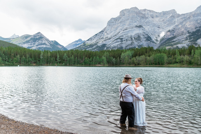 Bride and groom standing in the water holding one another, trees and mountains in the background.