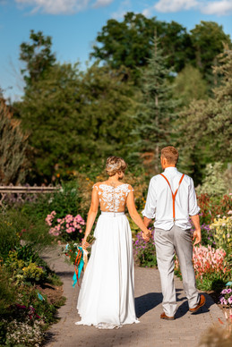 bride and groom walking down a pretty path hand in hand.