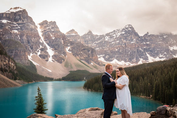 Bride and groom embracing on a big rock overlooking Moraine Lake and the mountains.