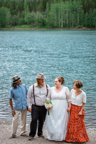 Wedding party standing in front of the water looking at one another smiling.