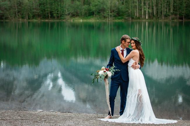 Bride and groom posing in front of the water in Kananaskis. Groom is looking at his bride.