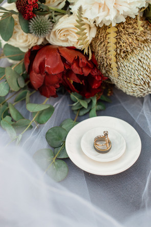 Bride and groom's rings on a dish against the brides veil and bouquet.