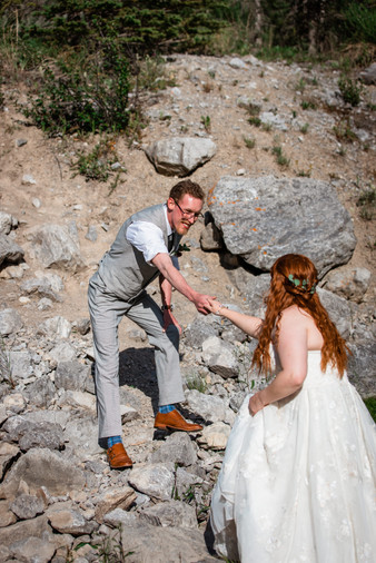 Groom helping his bride walk up some rocks.