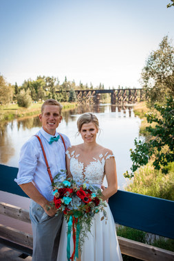 bride and groom standing on a suspension bridge with the water behind them.