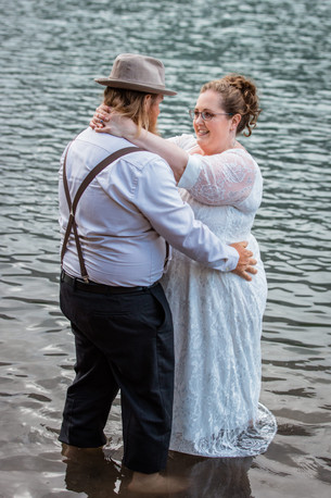 Bride and groom standing in the water holding one another.
