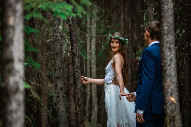 Bride and groom walking in the trees in Kananaskis, bride is looking back at her groom.