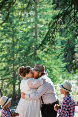 Bride and groom having their first kiss surrounded by trees.