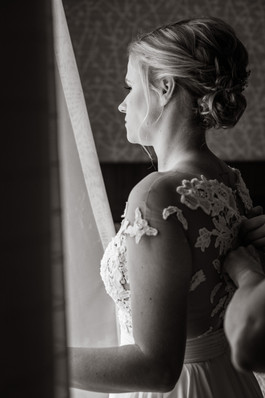 the bride looking away showing hands doing up her dress buttons.
