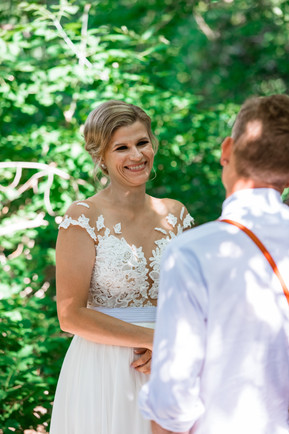 bride with a big smile looking at her groom as they sign their vows to one another.