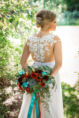 bride standing with her bouquet behind her back showing the beautiful details in the back of her dress.