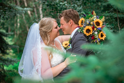 Bride and groom about to kiss. Sunflower bouquet is shown and the couple is surrounded by trees.