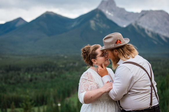 Groom leaning in for a kiss, holding his wife's cheek. Trees and mountains in the background.