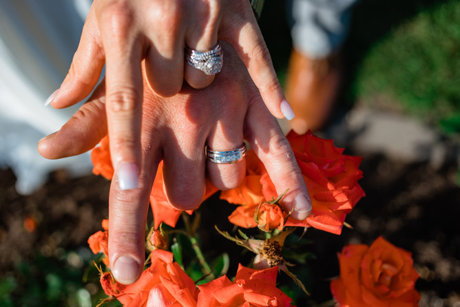 bride and groom rings and sign language for love against pretty flowers.